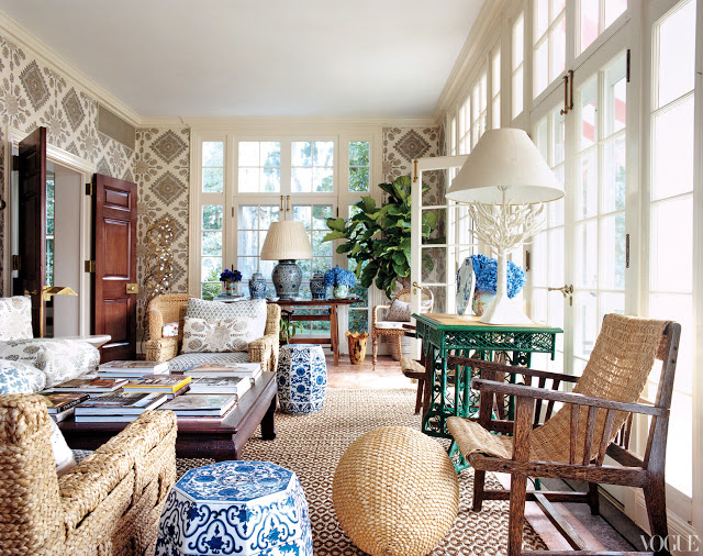 sun room with french doors, woven chairs, blue and white chinese garden stools, and quadrille wallpaper