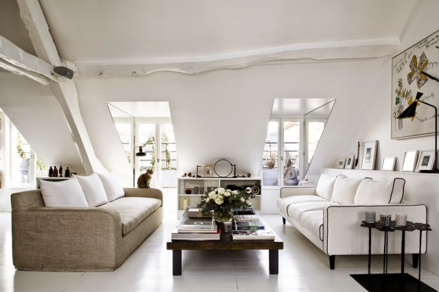 Living room in a Paris attic apartment with dueling sofas and yellow and black accents