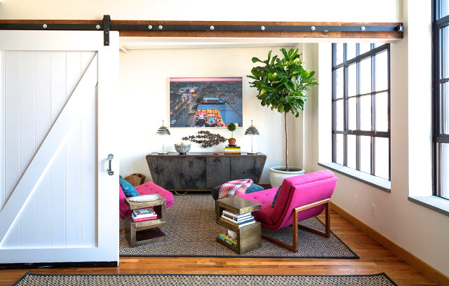 Anne Maxwell's nyc loft apartment den with pink lawson fenning chairs, wood floors, and a barn door