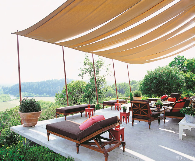 Canopy style shades cover an outdoor terrace that overlooks a hillside. Under the canopy are Moroccan style side tables and wood outdoor furniture
