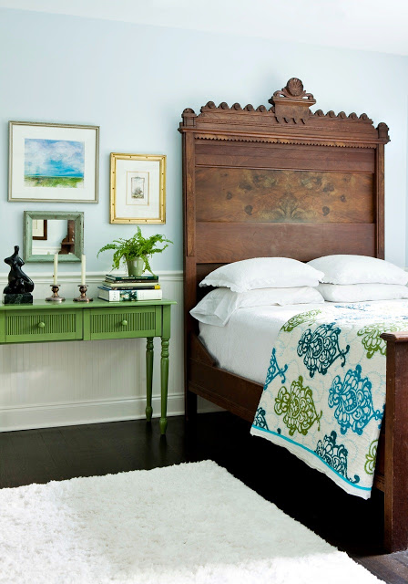 Bedrooom with antique wood headboard, green night stand, wood floors and a white rug