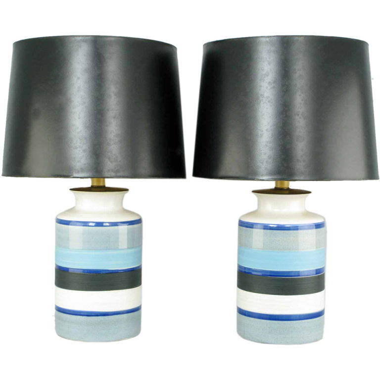 Two vintage table lamps have hand thrown pottery bodies, blue and black glazed horizontal stripes on a white ground and black shades