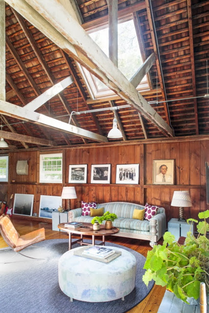 Living room with exposed beams and stained wood walls