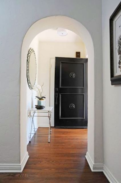 Foyer with black front door, arched entry way, wood floor a round mirror and a small table holding an orchid