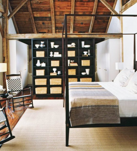 Bedroom with woven rocking chairs, canopy bed, open shelving with baskets, reclaimed wood floors and matching ceiling and exposed beams