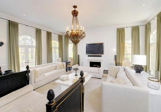 Family room with a wall mounted television, dueling white sofas, a chandelier, and lots of green drapes