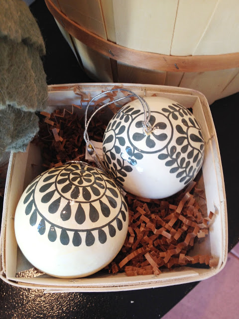 Two Christmas ornaments sitting in brown paper packing material in a white box