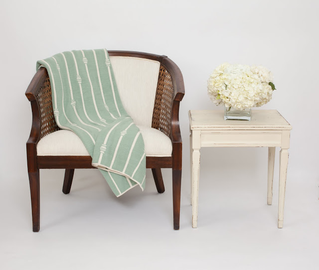 COCOCOZY throw elegantly placed on on upholstered wood chair next to a white vintage side table holding a glass vase of white hydrangeas