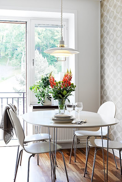 Breakfast nook in a small kitchen with a round white table, four chairs and a cute flower arrangement