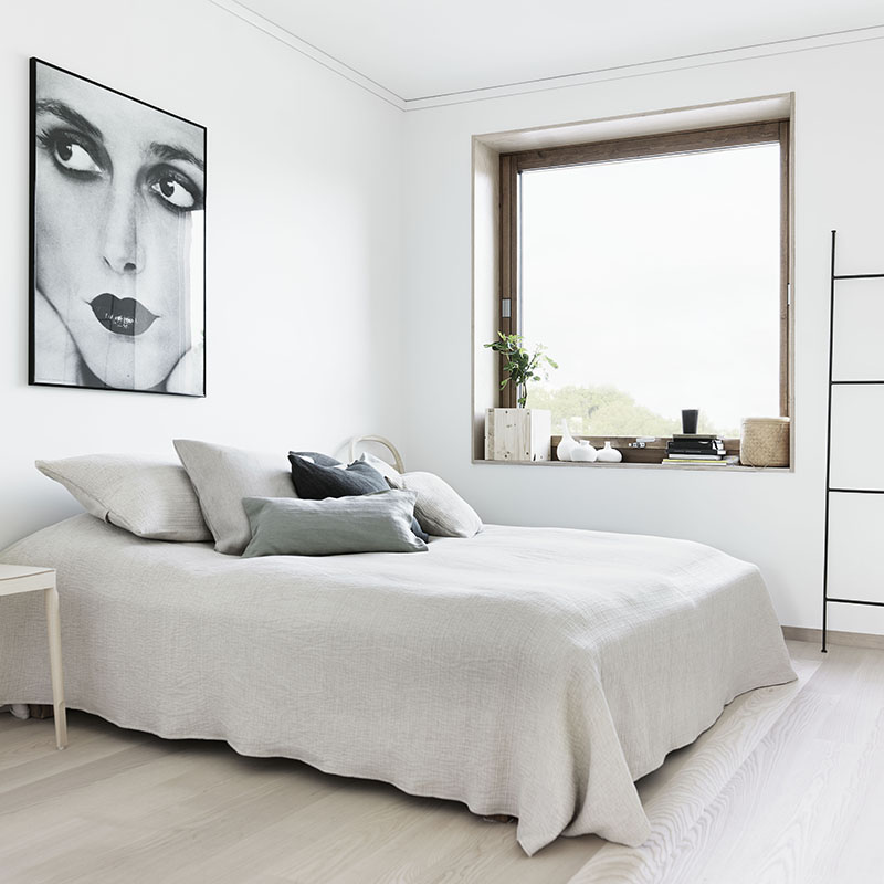 Beautiful Clean white bedroom with light wood floor a large window and a framed portrait