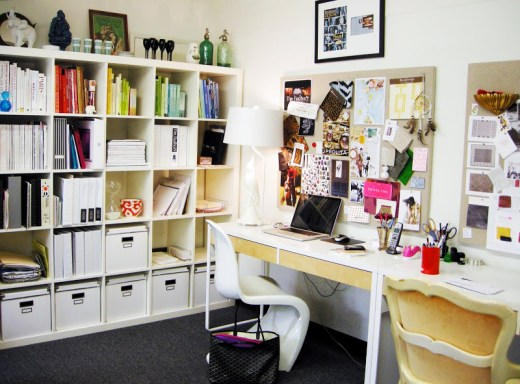 After the redecoration. A white Panton Chair is front of an Ikea found desk, to the left of the desk are shelves full of color coordinated books, files, and boxes