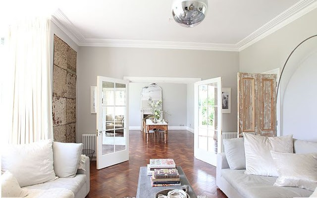alternate view of living room in a UK country house with walnut herringbone wood floors with a view into the dining room with gray walls