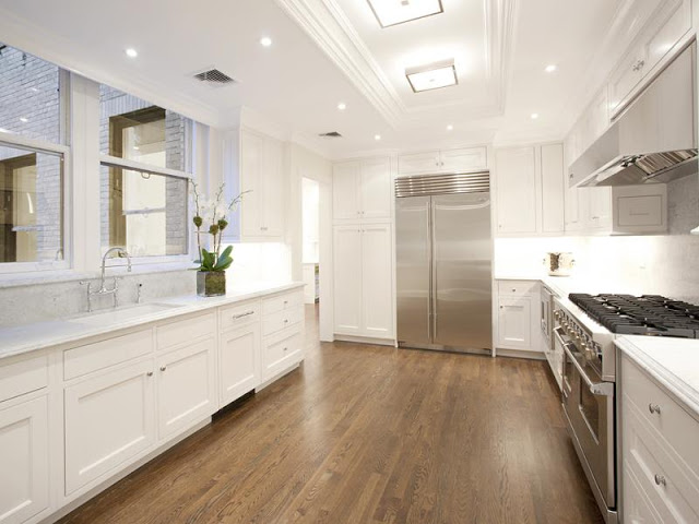 kitchen with Carara marble counters, stainless steel appliances, wood floors and recessed panel white cabinets
