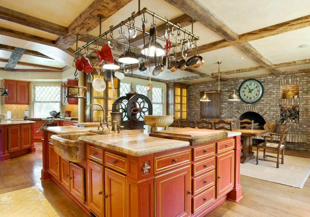 New rustic eat in kitchen in a mansion with red island cabinets stone fireplace