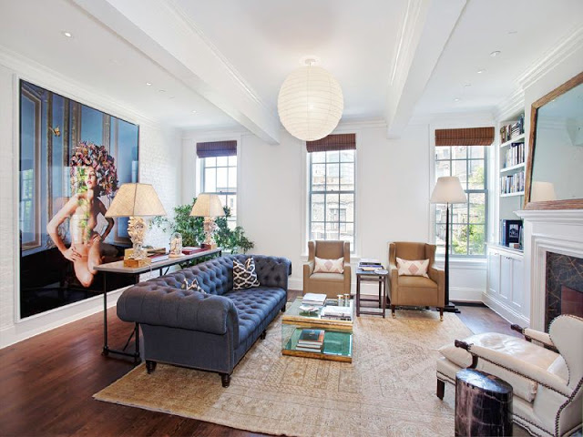 living room with black upholstered sofa, two brown armchairs, one white upholstered arm chair, a marble fireplace with a large mirror on the mantel and a white painted brick walls
