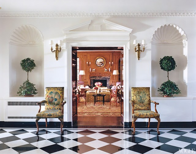 Main hallway with black and white checkered marble floor and a view into the wood paneled library