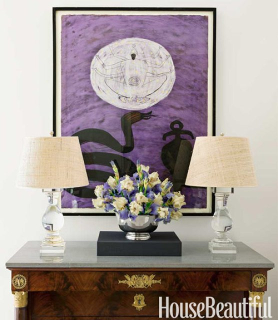Empire commonde with two lampes with a glass base and linen shades with a watercolor painting hanging between them