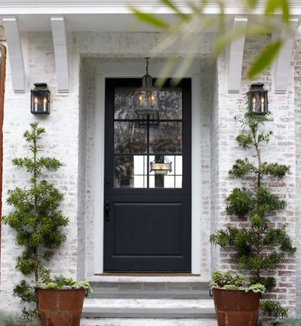 Entrace to a white washed brick house with rusty metal planters on either side, stone stairs, a black front door, and lantern style lights