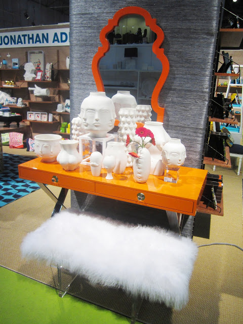 Jonathan Adler's Channing Desk in orange lacquer with white sculptures of Buddhas in front of a large orange mirror