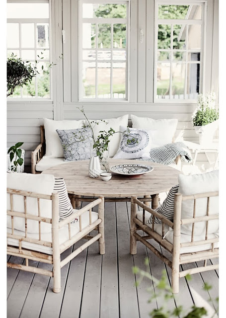 Grey front porch with grey wood furniture, stripped accent pillows and grey wood floor