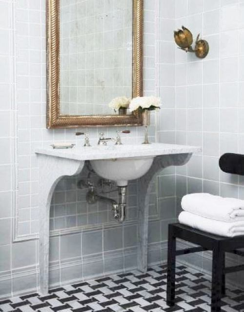 Bathroom with black and white marble mosaic floor and grey tiled walls, a wall mounted sink with an traditional antique mirror in a gold frame