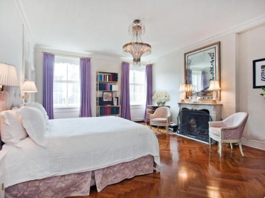 Master bedroom in a park avenue apartment with purple floor length curtains, a marble fireplace with a large vintage mirror on the mantel, a crystal chandelier and herringbone wood floor