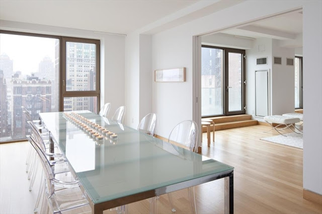 New York City penthouse dining room with ghost chairs, a glass top table, light wood floors, and a great view of the city