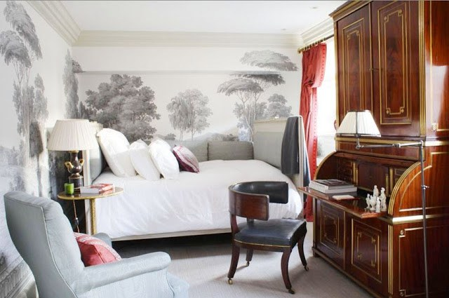 bedroom with pastoral wallpaper on the two visible walls, a white bed, a large wooden writing desk and red floor length curtain