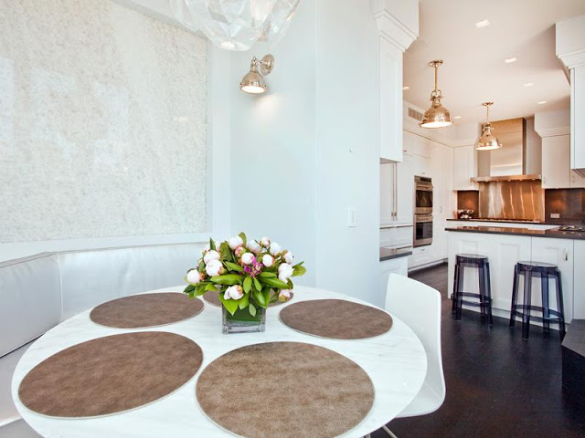 Breakfast nook and kitchen in an apartment with banquette seating around a white round table with a piece of modern art. The white kitchen has black counter tops, clear Kartell Lucite purple bar stools and two pendant lights