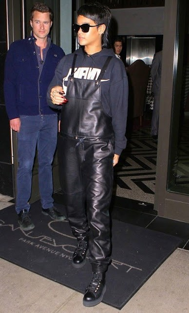 Rihanna wearing leather overalls and a navy sweater
