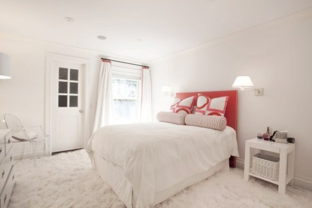 white bedroom with shag rug, nightstand, ghost Louis chair and red upholstered headboard