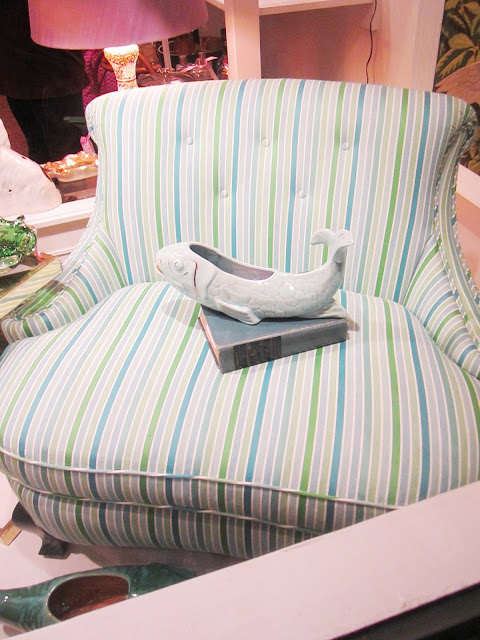 Close up of colorful blue, green and white striped settee in the window with a ceramic fish dish