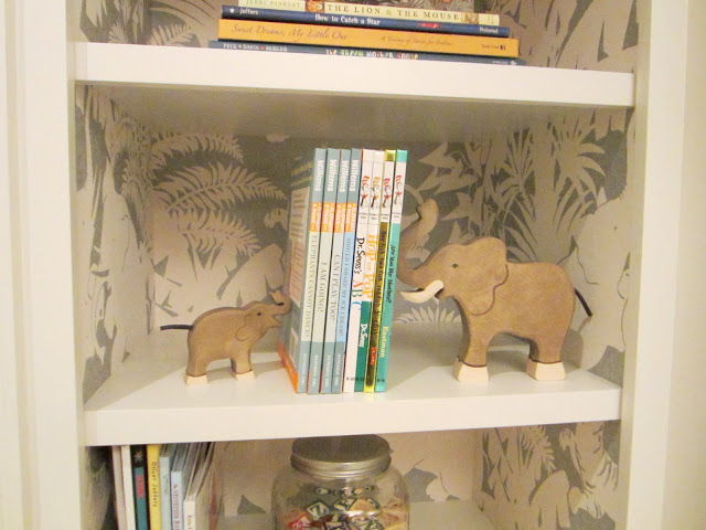 "Close up of Schumacher's ""Jungle Play"" wall covering in the built in bookshelves and elephant bookends in the baby room in the Windsor house"