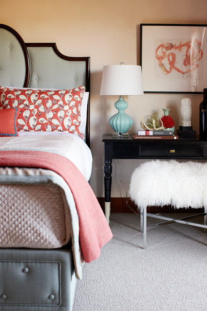 close up of nightstand with blue lamp with white shade and shag ottoman stool