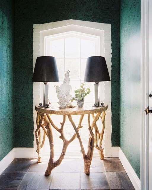 Malachite wallpaper in Kristi Bender's foyer with an organic circle table, parrot statues and two matching lamps with black shades