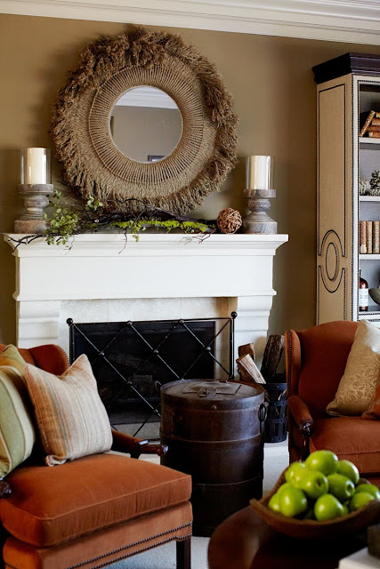 close up of fireplace with woven circle mirror and two candlesticks on mantel, diamond printed gate, a barrel converted into a side table and two orange chairs with neutral accent pillows