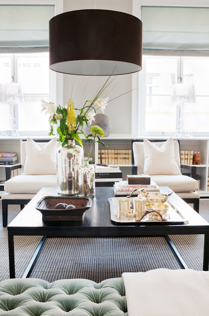 black drum style ceiling pendant light over a coffee table
