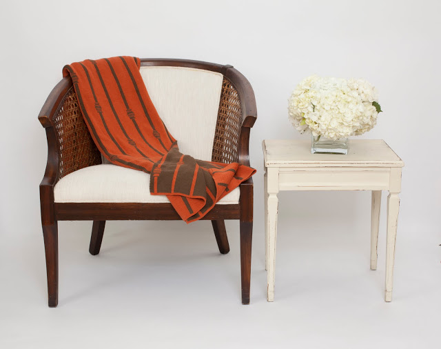 COCOCOZY throw draped across an upholstered wooden chair next to a vintage side table with a glass vase holding white hydrangeas