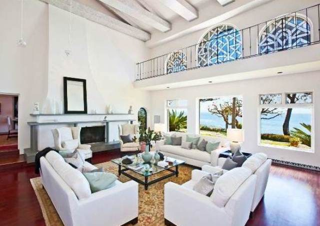 living room with exposed beams, dueling sofas, wood floors, a large area rug