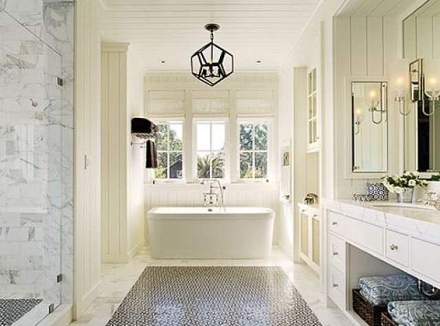 Bathroom with stand alone porcelain tub, marble floor, carpet mosaic tile and a black decahedron pendant light