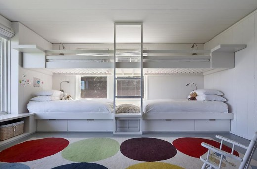 Kids bedroom in a lake house in Montauk on Long Island with two sets of white bunk beds with a ladder in between, a large poka dot rug and a white rocking chair