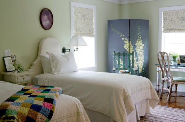 Twin bedroom with mint green walls, a wood floor, white upholstered Queen Anne style headboards, a large wardobe with a yellow flower painted on it and a vintage high back wooden chair in front of a reclaimed wood desk with a glass top