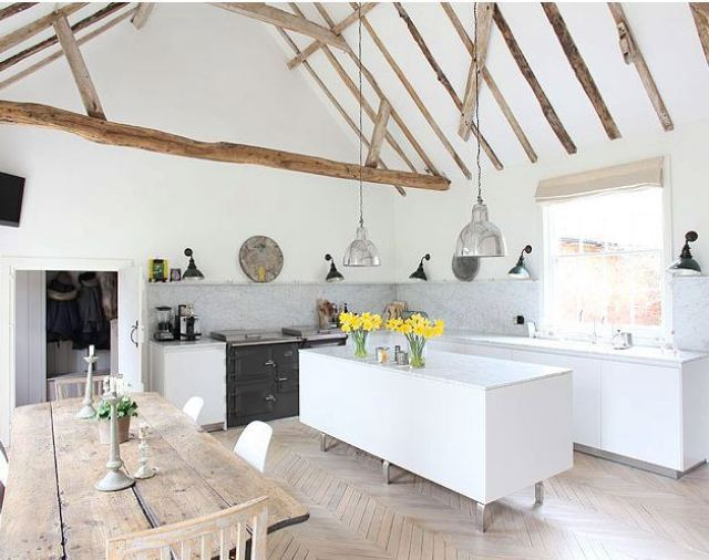 Kitchen with herringbone wood floor, exposed reclaimed wood beams, pendant lights, marble backsplash, an island and a large window