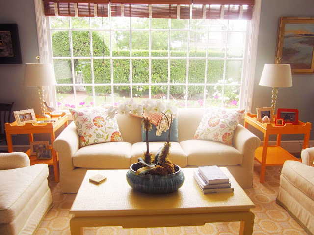 paned windows with bamboo shades, two yellow accent tables match the coffee table, a neutral sofa with blue and flower print accent prints.