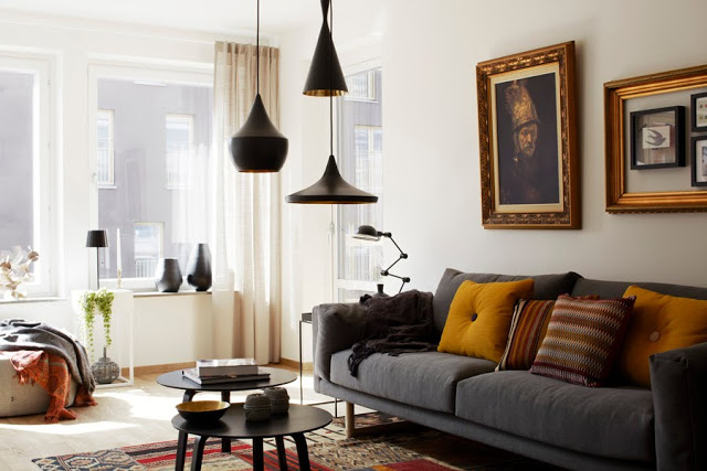 cluster of black pendant lamps over two coffee tables with a grey sofa with yellow accent pillows