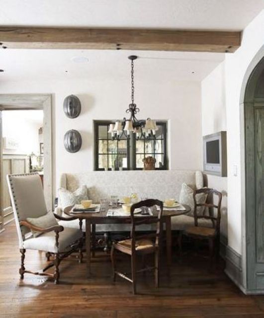Breakfast nook with exposed beams, stained wood floor, a wire chandelier, bench style seating on one side of an oval table with two wood chairs with rope seats and an upholstered arm chair with nail head trim on the other