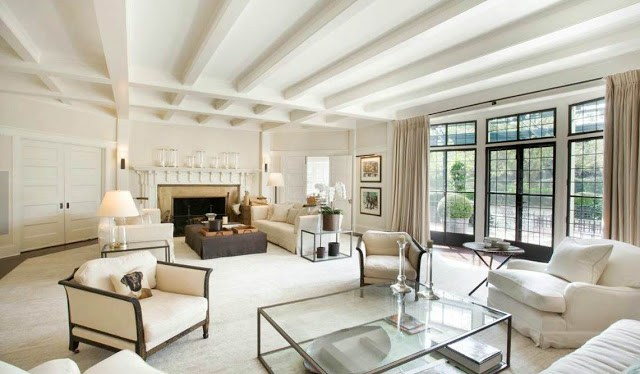 living room in a mansion with off white color scheme, large encasement windows and french doors with black trim, a fireplace and visible beams