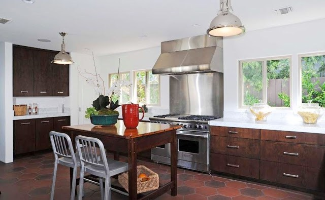 Kitchen with hexagon Saltillo tiles on the floor, stainless appliances, dark wood cabinets with silver drawer pulls and white counter tops and two silver pendant lights. Instead of an island, there is a wood table with two metal chairs