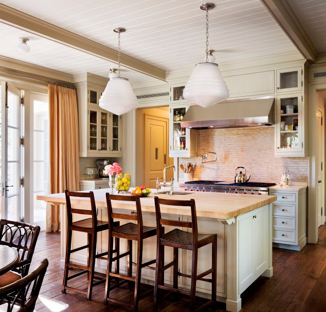 Kitchen from Kitchens and Baths by Michael S. Smith with two pendant lights, an island with wood counter top and white cabinets, stainless appliances, a brick backsplash, french doors and wood floors