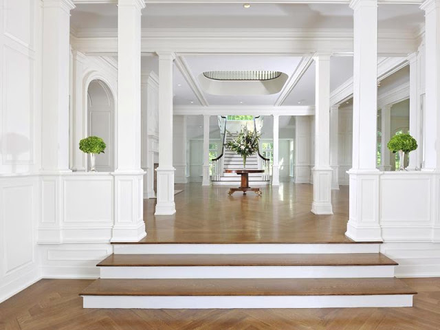 alternative view of the foyer with white grand staircase, fire place and herringbone wood floor